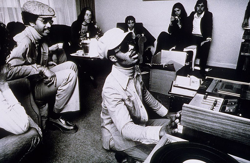 Stevie Wonder puts on a cassette for friends backstage